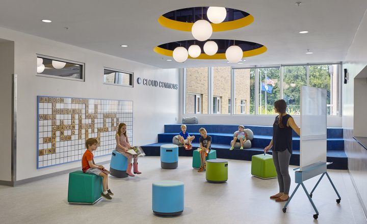 Detroit Country Day School VIVID classroom renovations. Students sit on colorful cubes to learn in the Cloud Commons from a teacher standing at a white board.