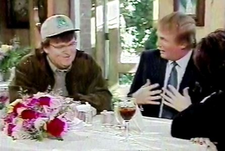 Still from the movie Fahrenheit 11/9 of Donald Trump talking to two people at a fancy meal, one of which is Michael Moore.