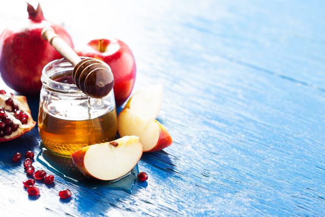 Rosh hashanah (jewish holiday) concept: honey, apple and pomegranate, with space for textRosh hashanah (jewish holiday) concept: honey, apple and pomegranateRosh hashanah (jewish holiday) concept: honey, apple and pomegranate