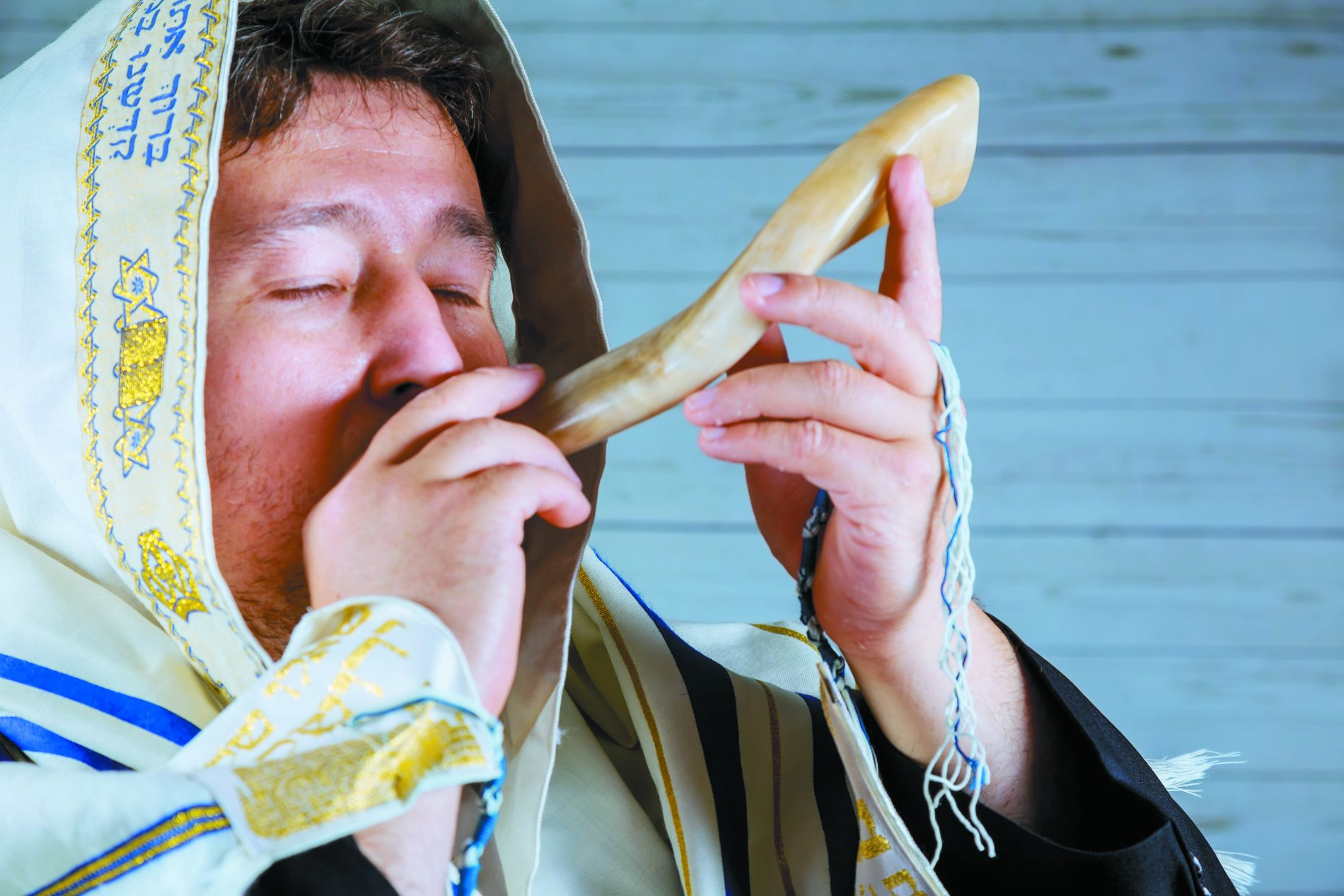 Jewish man blowing the Shofar horn of Rosh Hashanah New Year . Religious symbol.. High holidays music.