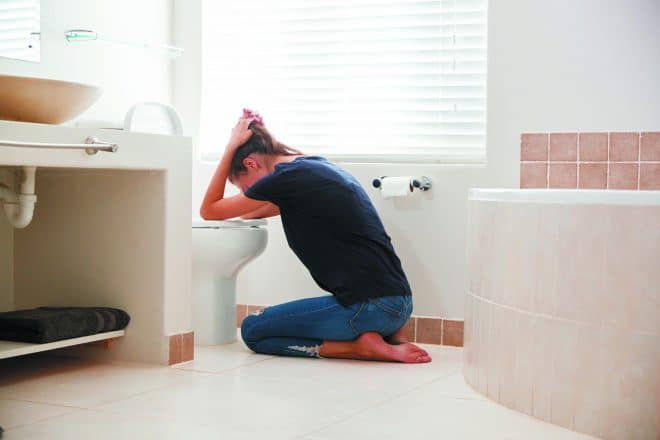 Woman Suffering With Morning Sickness In Bathroom At Home. Eating disorder.