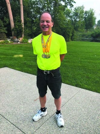 Jim Berk shows off the swimming medals he won last month at the Michigan Senior Olympics.