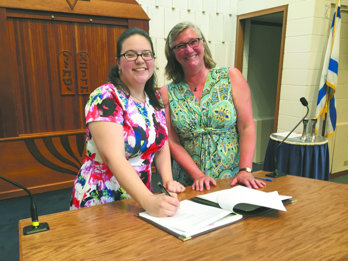 Rabbi Simone Schicker signing her contract with Joan Hawxhurst, immediate past president of Temple B'nai Israel