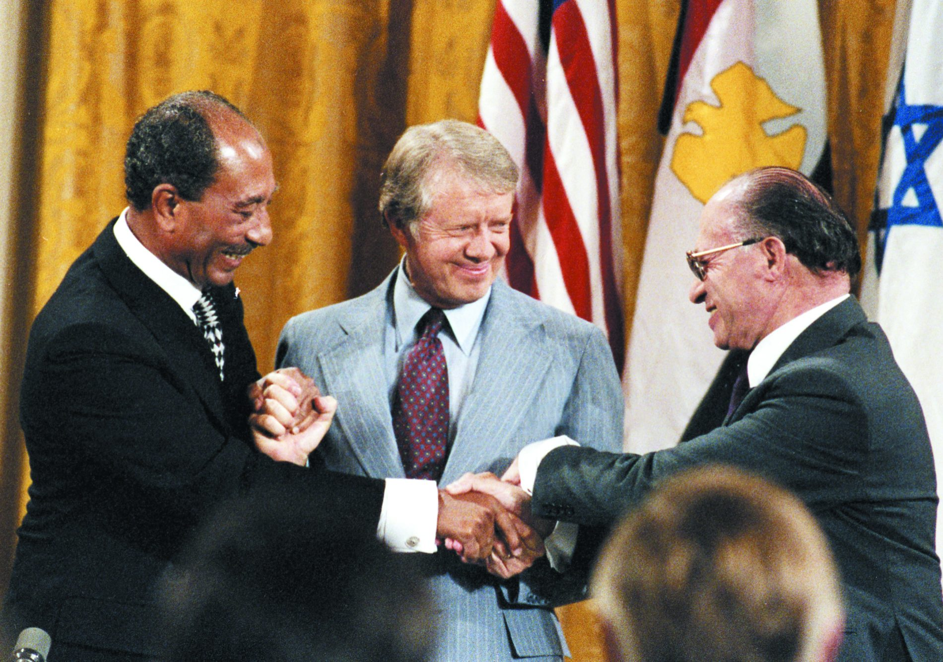 Egyptian President Anwar al-Sadat, left, and Israeli Prime Minister Menachem Begin, right, shake hands after signing the Camp David Accords 40 years ago at the White House, with U.S. President Jimmy Carter as the broker who signed the historic accord as a witness.