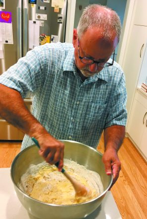 Marc Sussman mixes dry ingredients with the wet yeast mixture while making his challah dough.