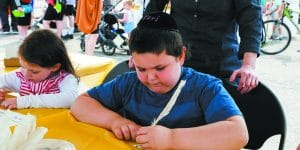 : Tzvi Pollack, 5, of Brooklyn, N.Y., works with ink and a feather pen to draw Hebrew letters.