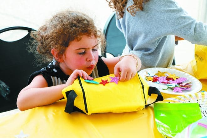 Raya Ita Salita, 3, of West Bloomfield decorates a small tote.