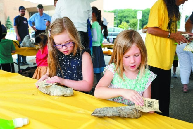 Eliyana, 7, and Mikaela Townsley, 4, of Clarkston use sandpaper to smooth their ram's horns.