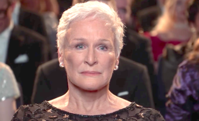 Still from the movie The Wife showing Glenn Close looking seriously into the camera. She plays Joan Castleman.