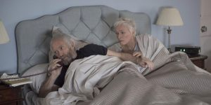 Still from the movie The Wife showing Glenn Close as Joan Castleman and husband Joe in bed. Joe is talking on the phone and Joan is watching him with interest.