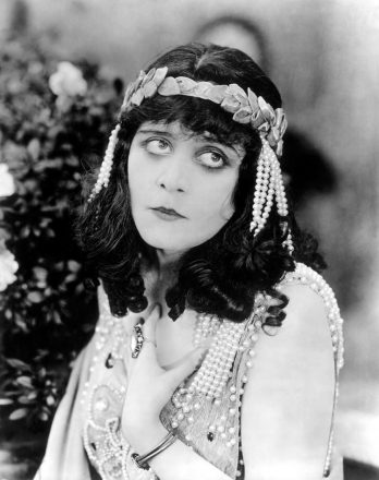 1918: American actor Theda Bara (1885-1955) looks up, holding one hand to her chest in a still from director J. Gordon Edwards' silent film 'Salome'. She wears a garland headband with pearls hanging from her hair and shoulders.