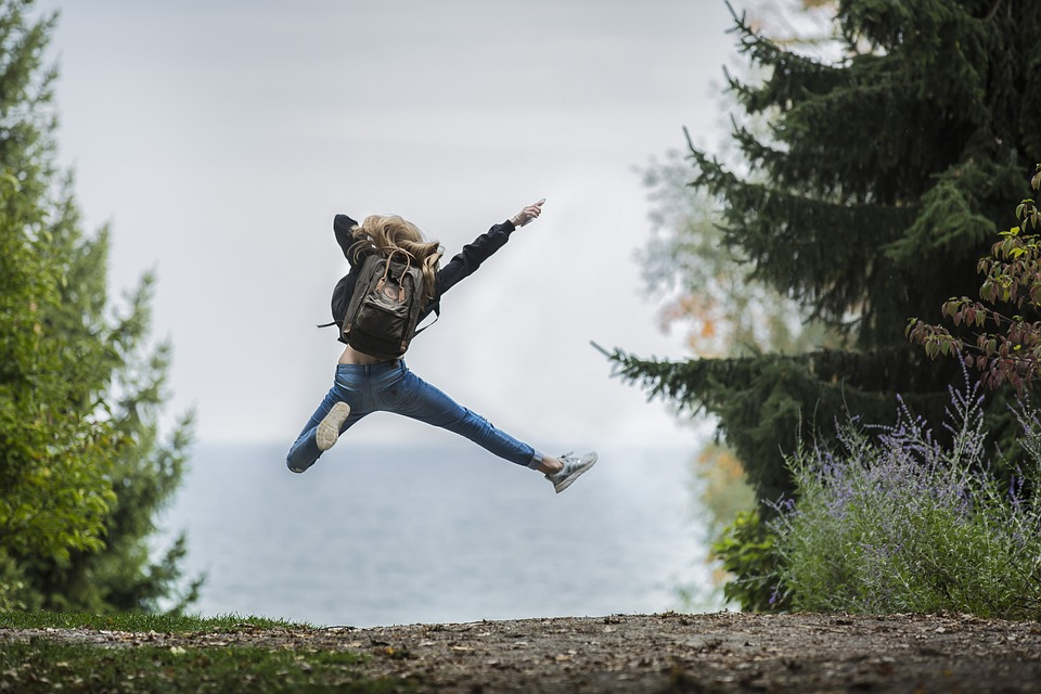 woman jumping for joy near some pine trees and overlooking some body of water