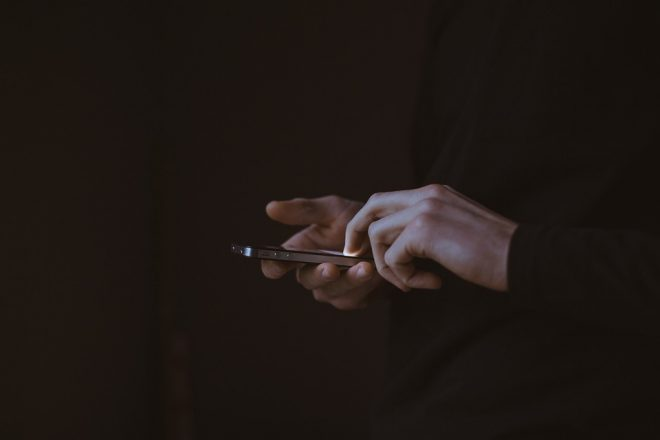 person's hands holding a cellphone in a dark area lit by the light from the cellphone.