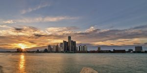Detroit skyline with water and rocks at sunset