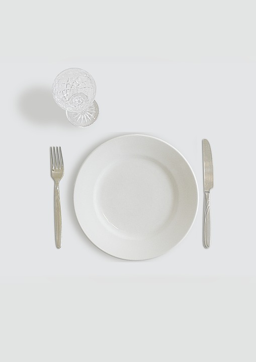 empty plate with fork and knife and empty glass.
