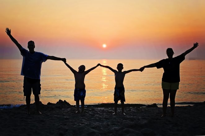 Come Together. A family holds hands on a beach in front of a sunset.