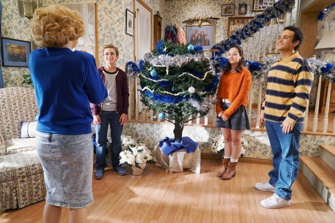 The children from The Goldbergs smile next to a Hanukkah decorated tree called a Hanukkah bush as Beverly Goldberg looks upon the tree with joy.