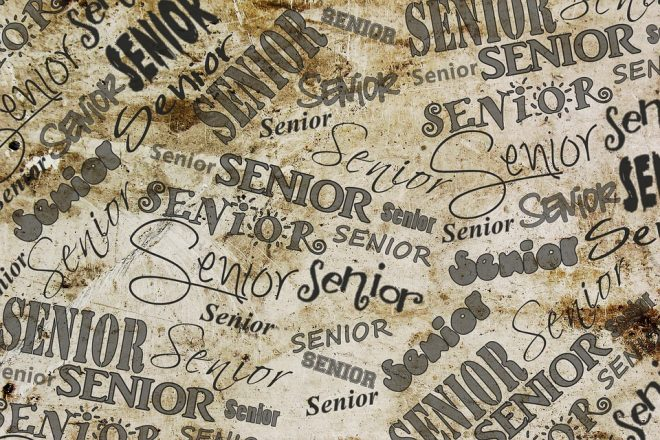 "the word ""senior"" written over and over in different fonts on something that is meant to look like a desk."