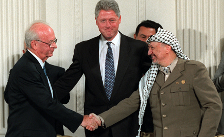 Prime Minister Yitzhak Rabin and PLO leader Yasser Arafat shake hands in from of President Bill Clinton at the White House after signing the Israeli-Palestinian Interim Agreement (Oslo II).