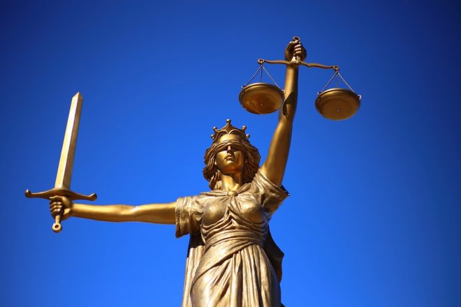 Lady Justice statue holds a sword and a balance in front of a clear blue sky.