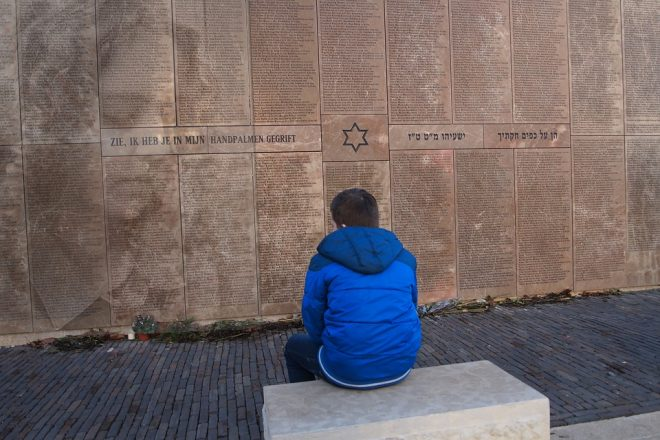 a boy sits at a Holocaust memorial in reflection to represent the reflection that goes on during Tishrei and the goal to never forget the 6 million Jews who died during the Holocaust