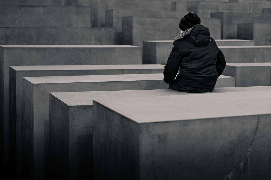 woman sits on concrete blocks at a Holocaust