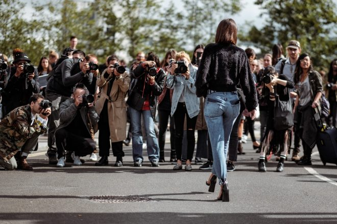 woman walking towards a group of people all taking her photo. Paparazzi