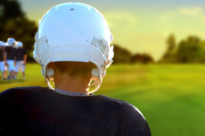 football player wearing helmet on the field seen from behind as he looks at a few other players and the setting sun.