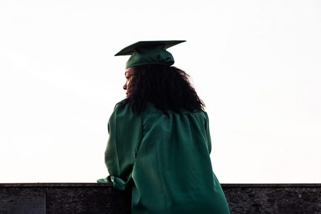 woman in cap and gown stares off into the distance.