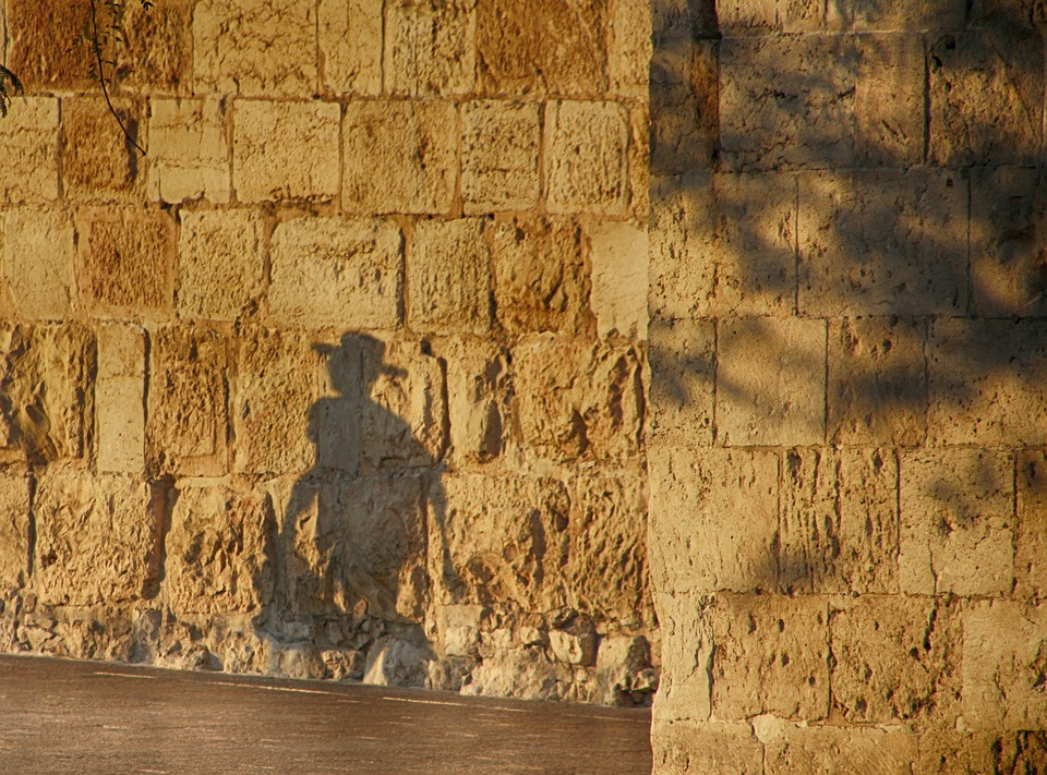 shadow of a boy in a hat running on the Western Wall in Jerusalem