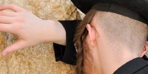 Jewish man praying at the Western Wall with his head and hand against the wall viewed from behind.