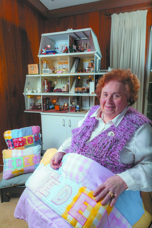 Sharon Blatt with some of her handmade, personalized blankets and pillows; her stylized dollhouse in the background became a replica of her own house.