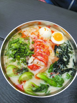 bowl of noodles from Ima Noodle Bar with veggies and an egg.