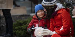 a woman and a child smile with a lit candle