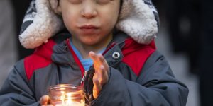 a child holds a candle