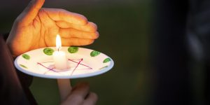a lit candle is held with a paper plate with a star of David on it and a hand to block the wind.