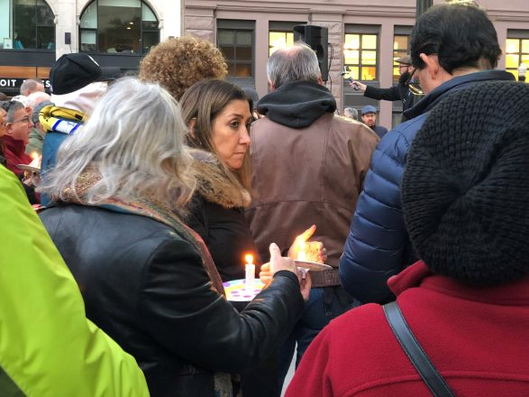 people gather for a vigil honoring the victims of the Tree of Life synagogue shooting with lit candles.
