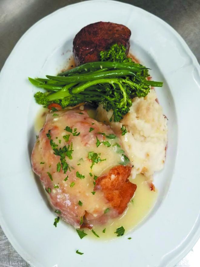 chicken on a plate with mashed potatoes and broccolini