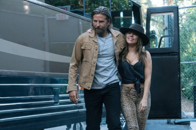 Bradley Cooper as Jackson Maine and Lady Gaga as Ally in A Star is Born still showing the two walking together arm in arm.