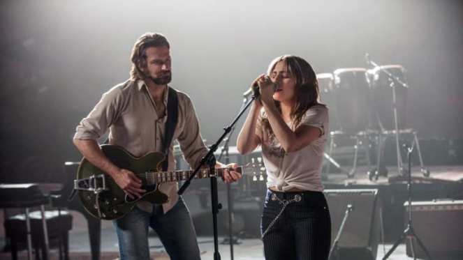 Bradley Cooper as Jackson Maine and Lady Gaga as Ally in A Star is Born still showing the two singing together on stage.