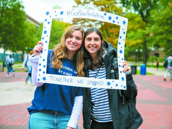 Junior Noa Friedman of White Plains, N.Y., a pro-Israel activist, and sophomore Emily Reisler of Chicago pose for the #GoBlueAndWhite social media campaign Oct. 11 on the Diag at U-M in response to the recent anti-Israel incidents on campus.