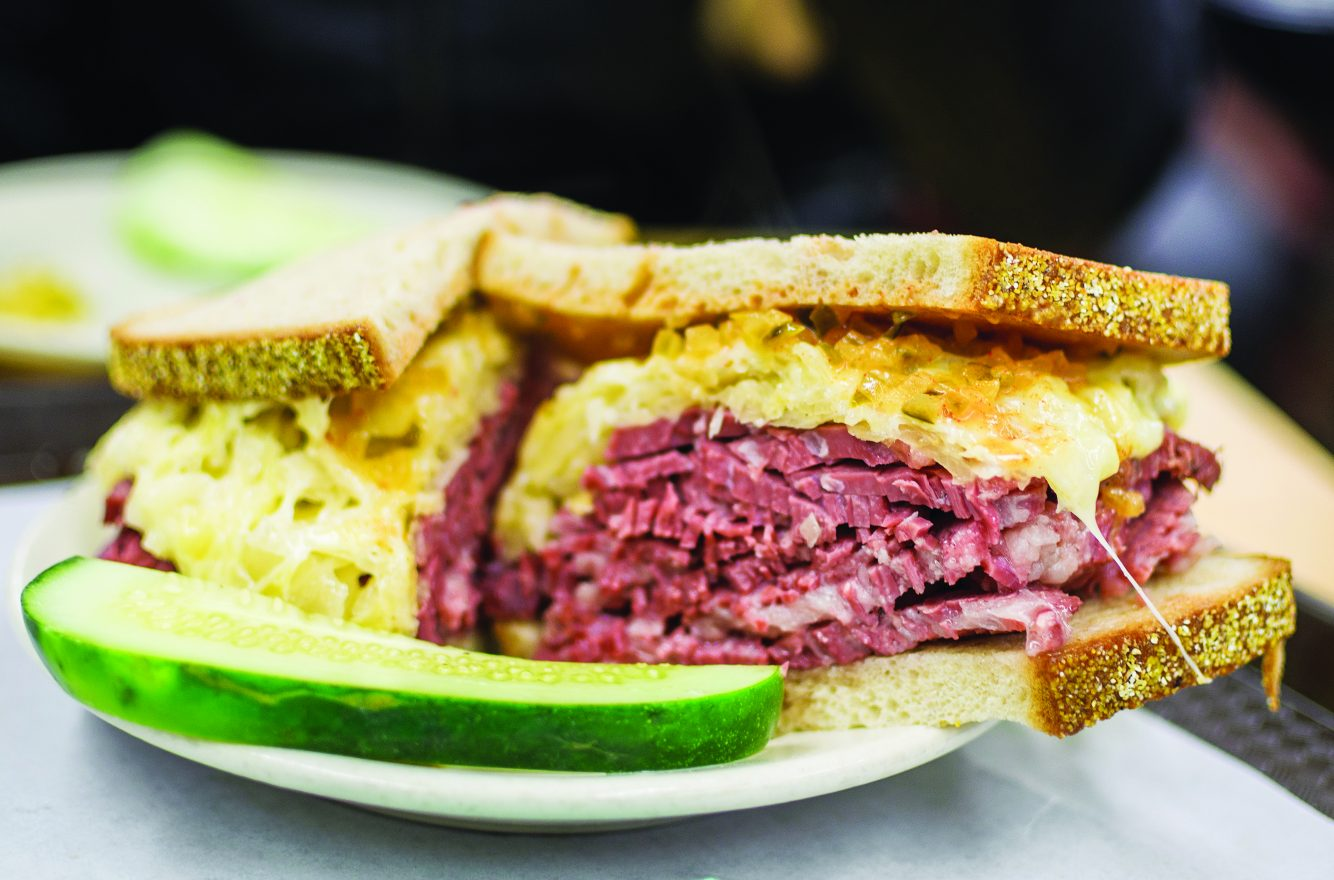 deli sandwich with pastrami or corned beef and macaroni and cheese with a pickle on the side.