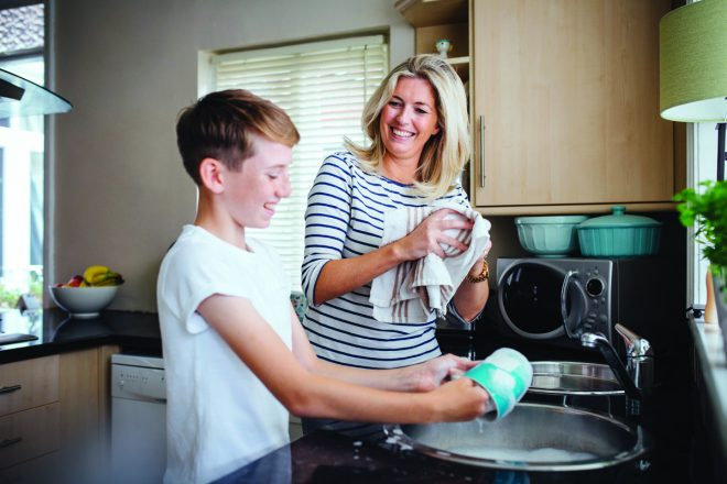 Mother and son doing the dishes together. They are talking and laughing as the boy washes and the mother dries dishes.
