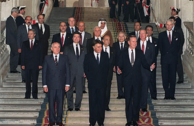 Men from the Soviet Union, the United States, Israel, and the PLO stand on the steps of the Madrid Middle East Peace Conference