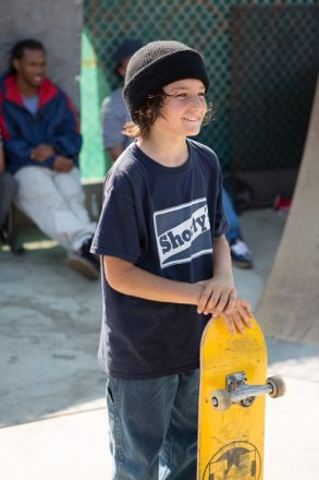 Still from the movie Mid90s with a kid smiling as he holds a skateboard. The child's name is Stevie and he is the protagonist of the movie played by Sunny Suljic.