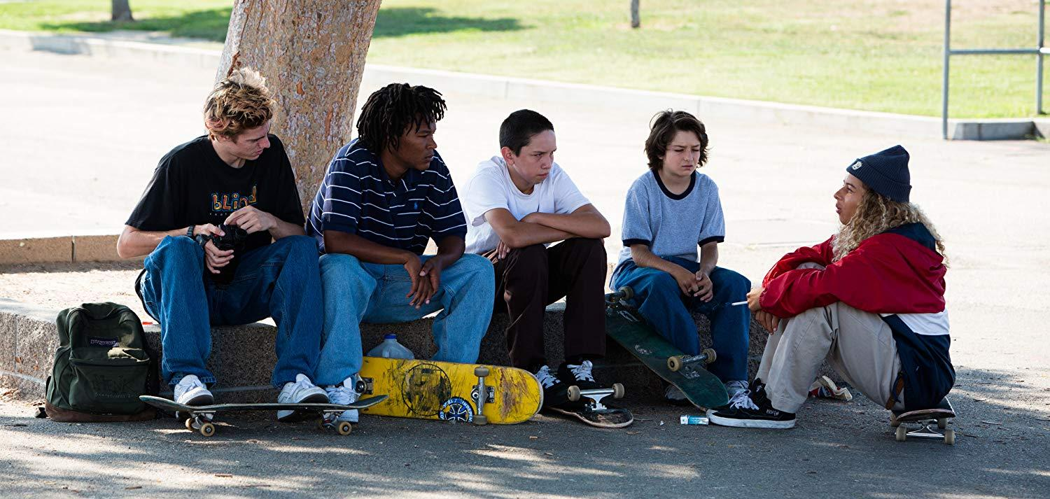 still from the movie Mid90s with 5 kids sitting near a tree with skateboards.