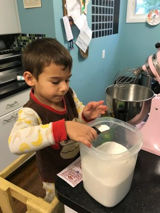 C pours flour into the mixing bowl to make challah