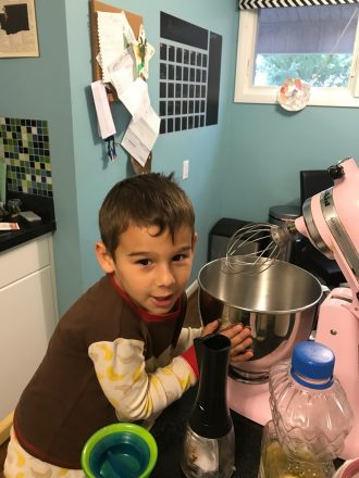 C holds a mixing bowl beside a mixer