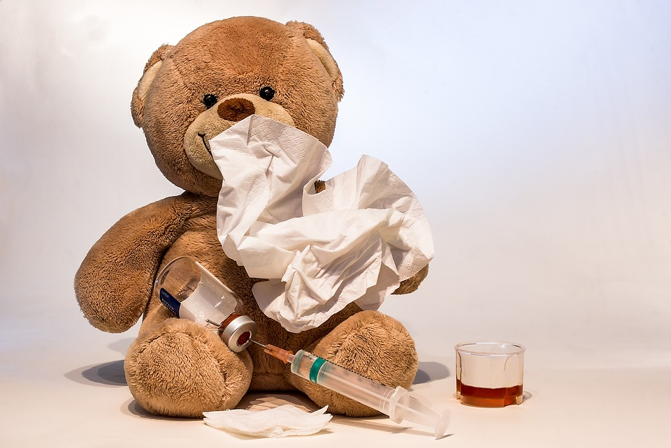 teddy bear with a tissue and a shot next to him to show a flu vaccination