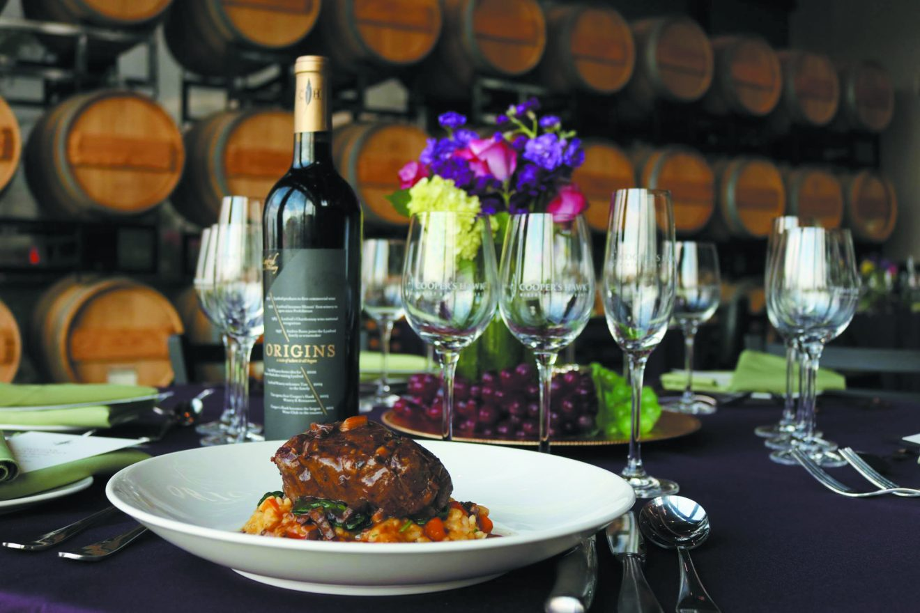 Wine glasses and a bottle of wine with a plate of filet at the Cooper's Hawk Winery & Restaurant